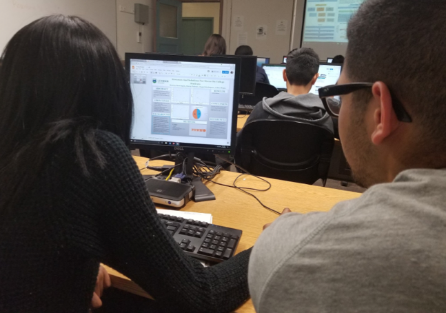 Two students are looking at a poster template on a computer screen.